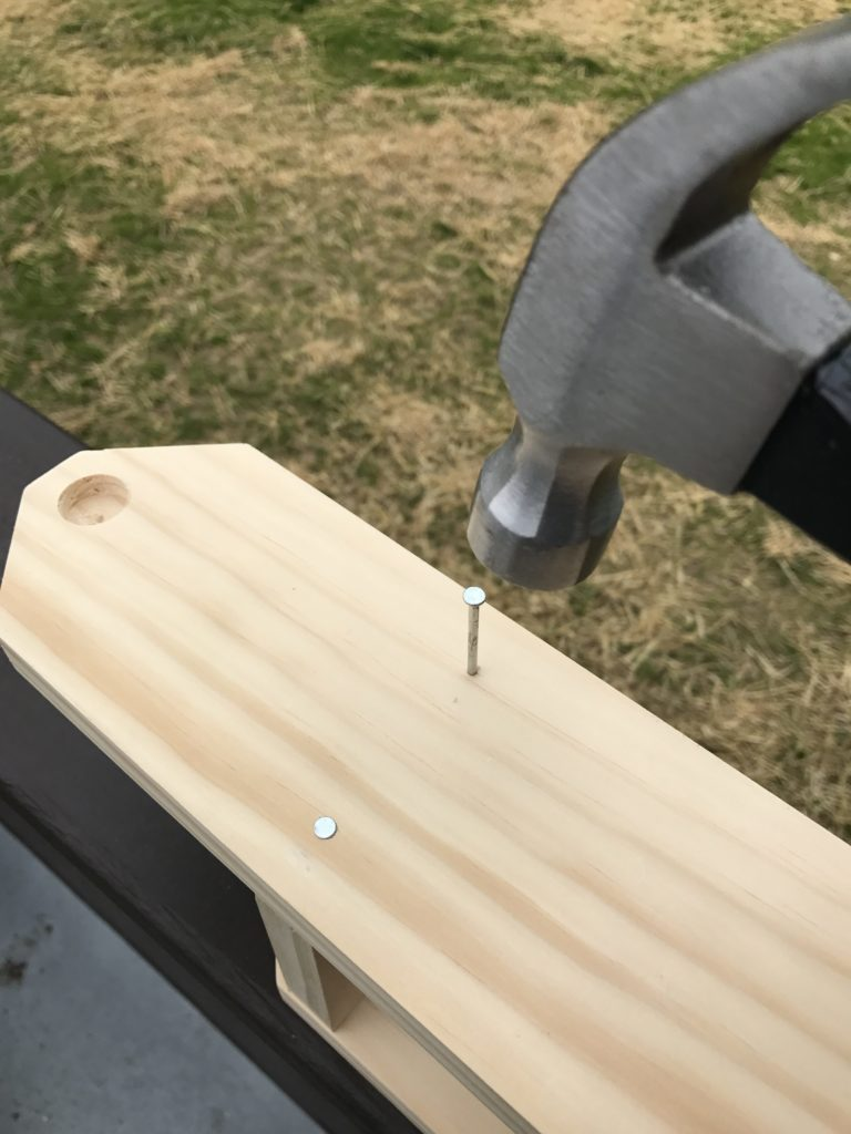 nailing nail into side of two glass wine caddy