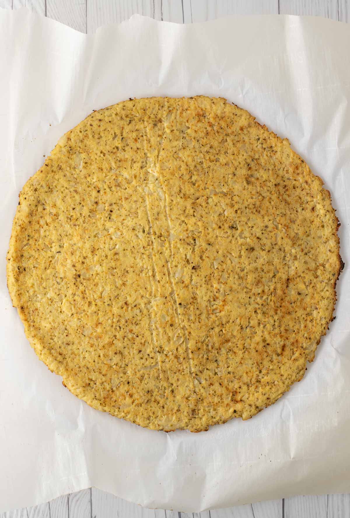 overhead shot of cauliflower crust on parchment paper