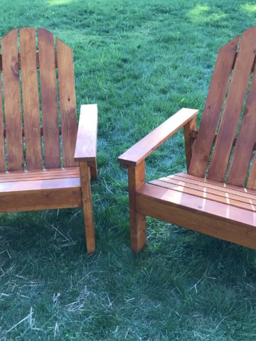 two homemade Adirondack chairs that are stained