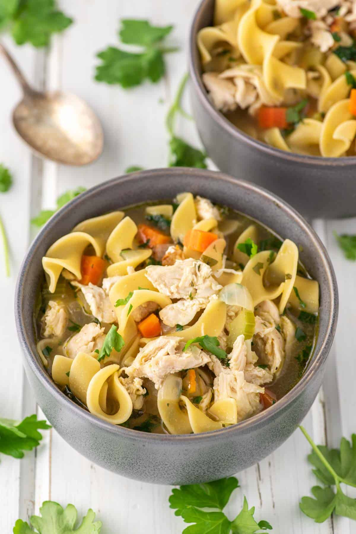 two bowls of soup with chicken and noodles