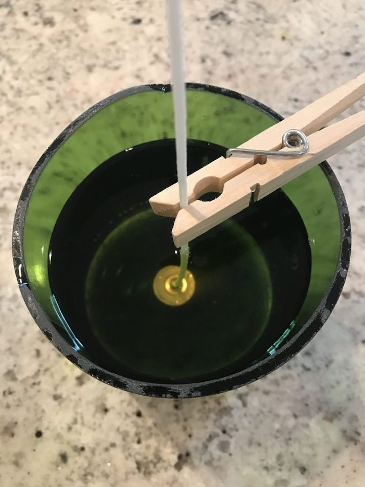 close-up of closing pin holding wick with melted wax in glass for soy candles