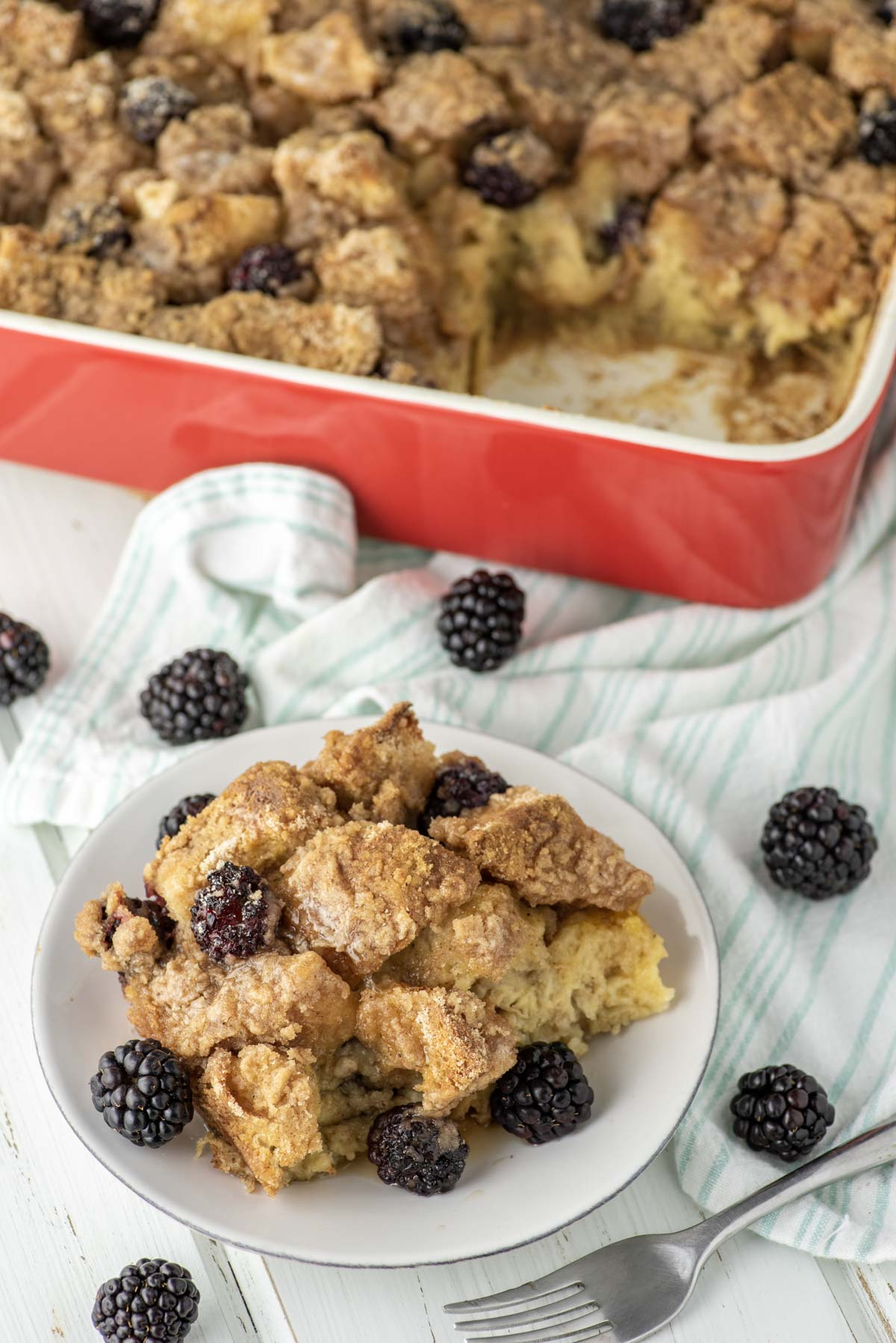 blackberry french toast casserole on plate with 9x13 dish in background