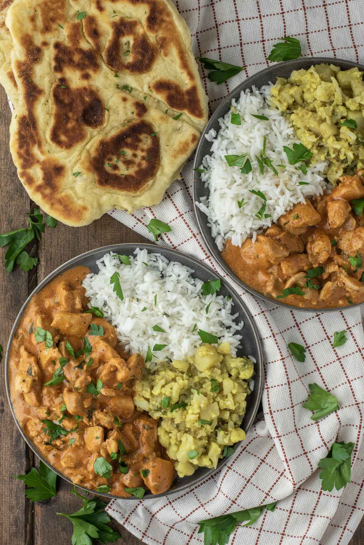 overhead shot of two plates of chicken tikka masala with rice and aloo gobi