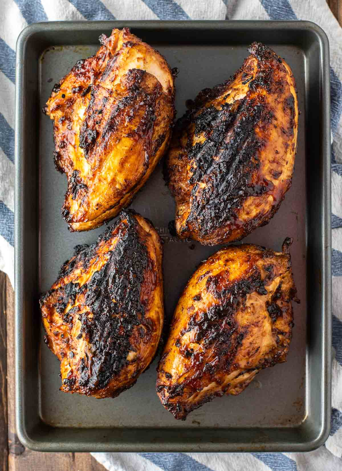 overhead shot of grilled BBQ chicken on baking sheet