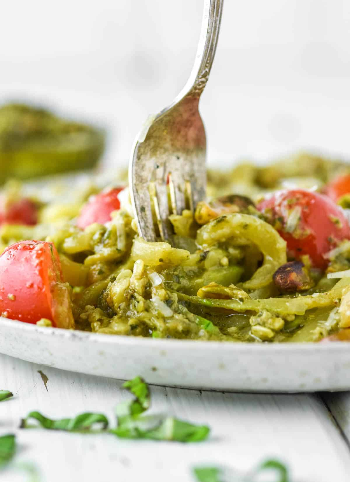 fork dipped in spiralized zucchini with pesto on plate