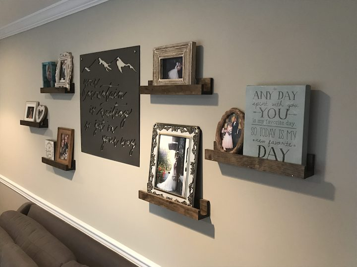 floating wood shelves on wall with pictures and art