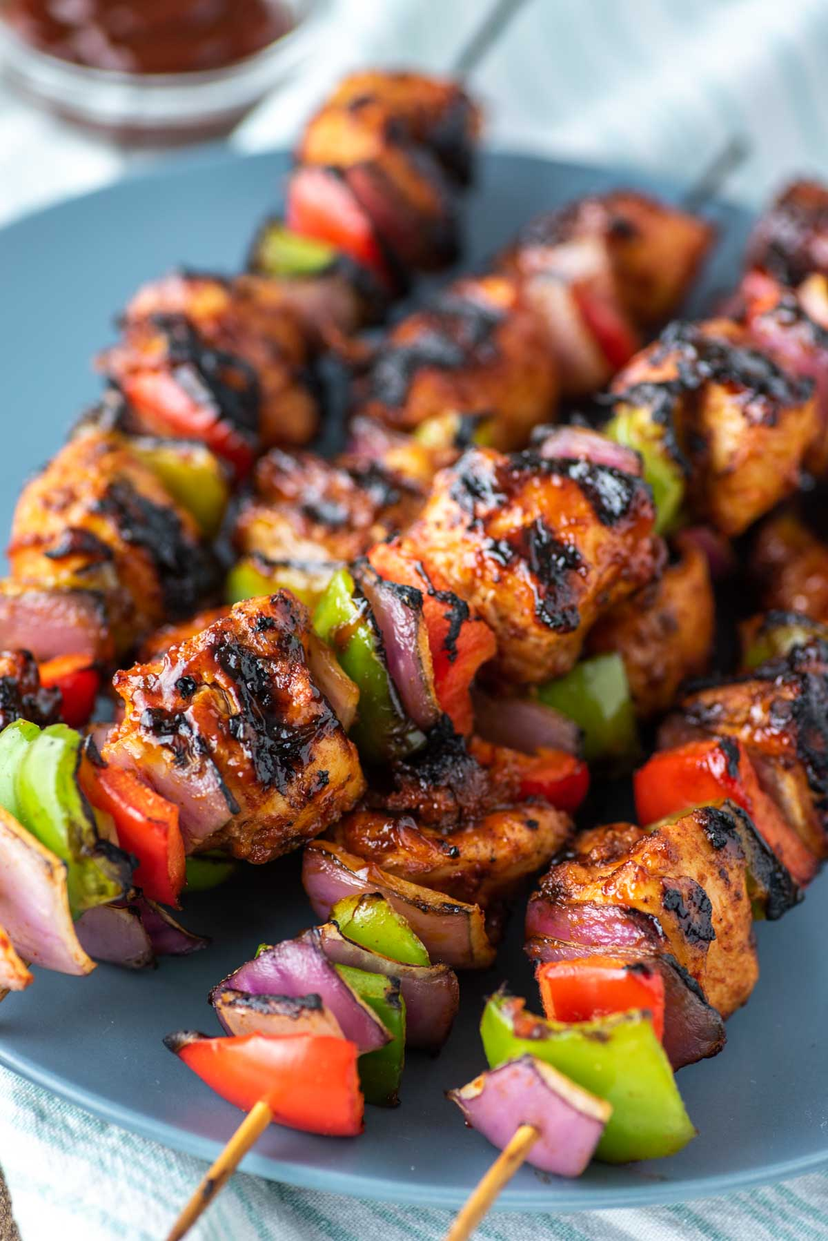 close-up of BBQ chicken kebabs on grey blue plate