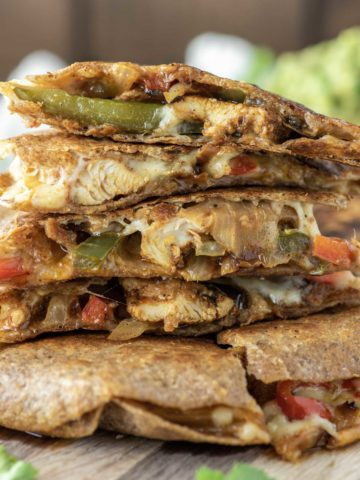 chicken fajita quesadillas stacked on cutting board