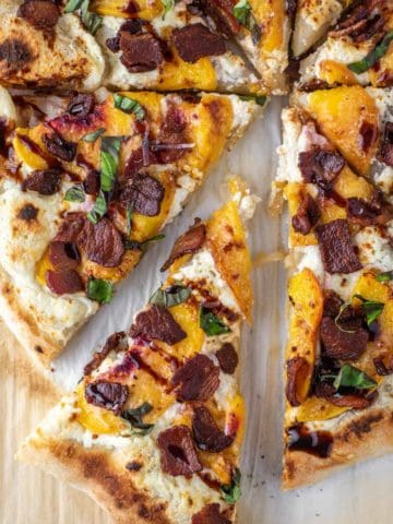 overheat shot of slice of peach pizza being pulled away on parchment paper