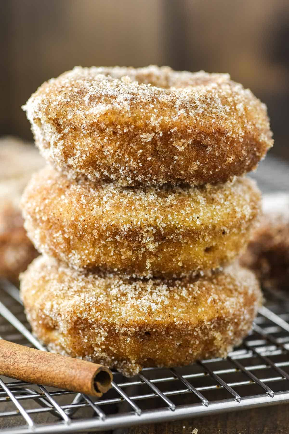 3 apple cider donuts stacked on cooling rack