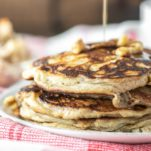 maple syrup drizzled on stacked apple ricotta pancakes