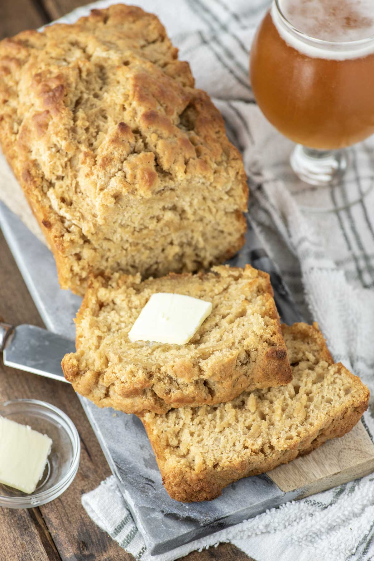 sliced beer bread on serving tray with slice of butter
