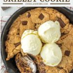 overhead shot of spoon dipped in chocolate chip peanut butter skillet cookie with ice cream