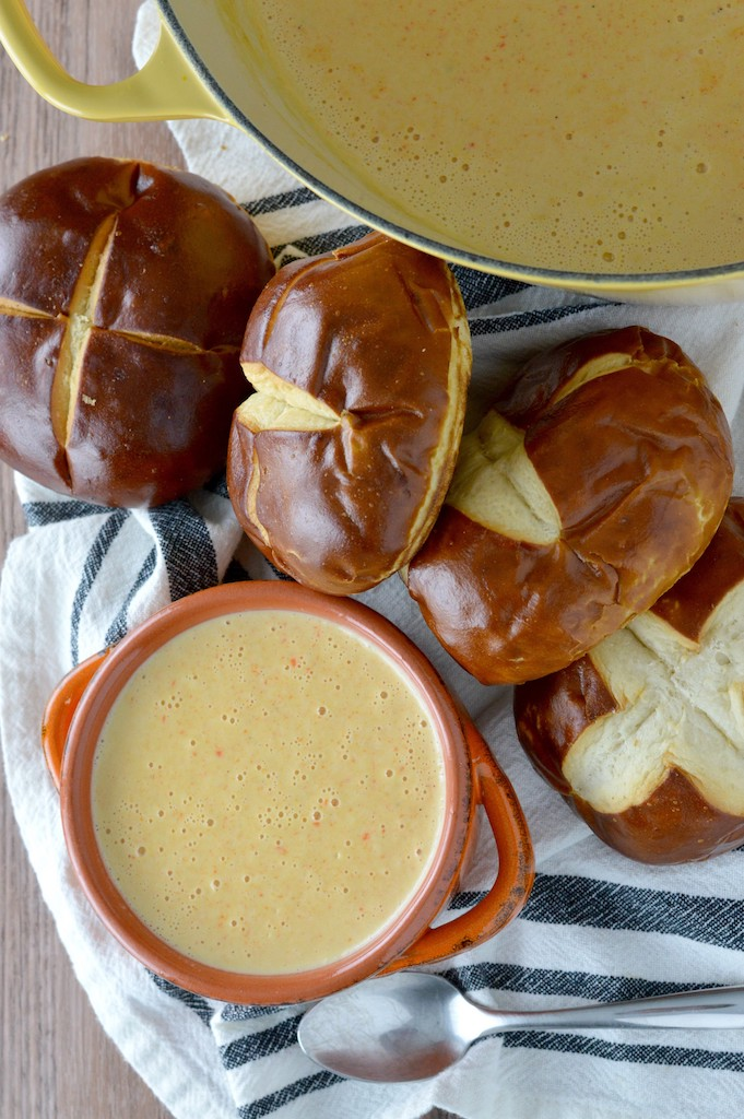 overlay of beer cheese soup recipe in orange bowl with pretzels