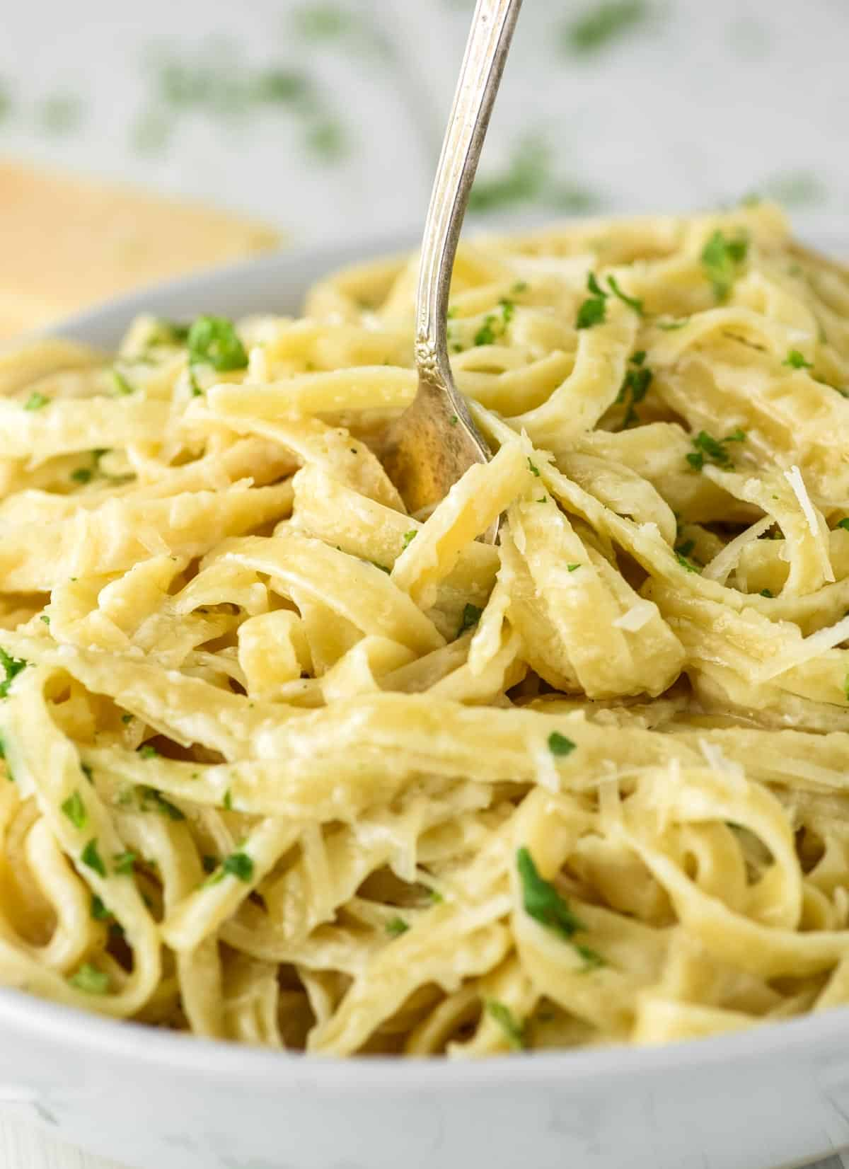 fork twirling fettuccine with alfredo sauce out of bowl