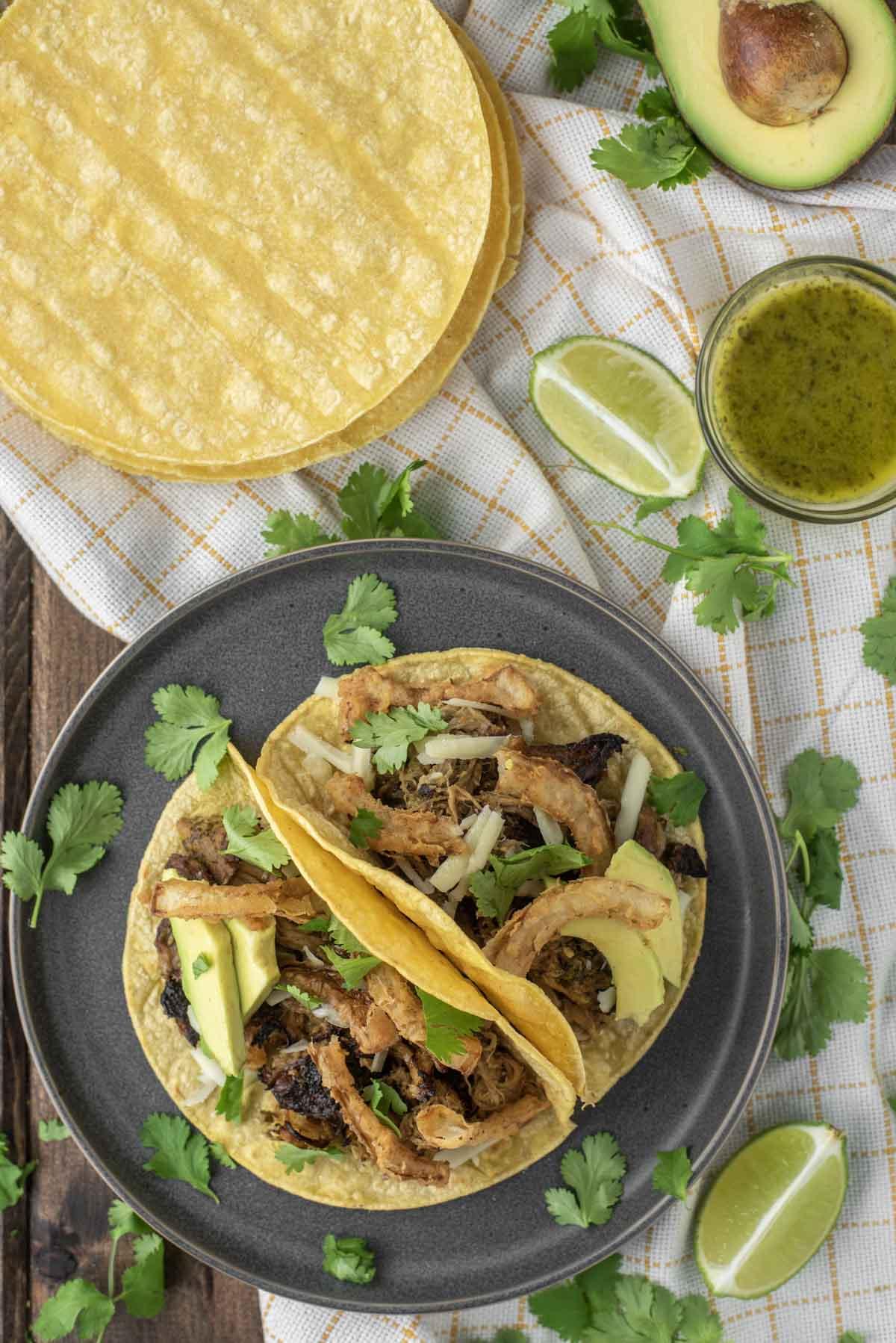 overhead shot of pork tacos on slate grey plate