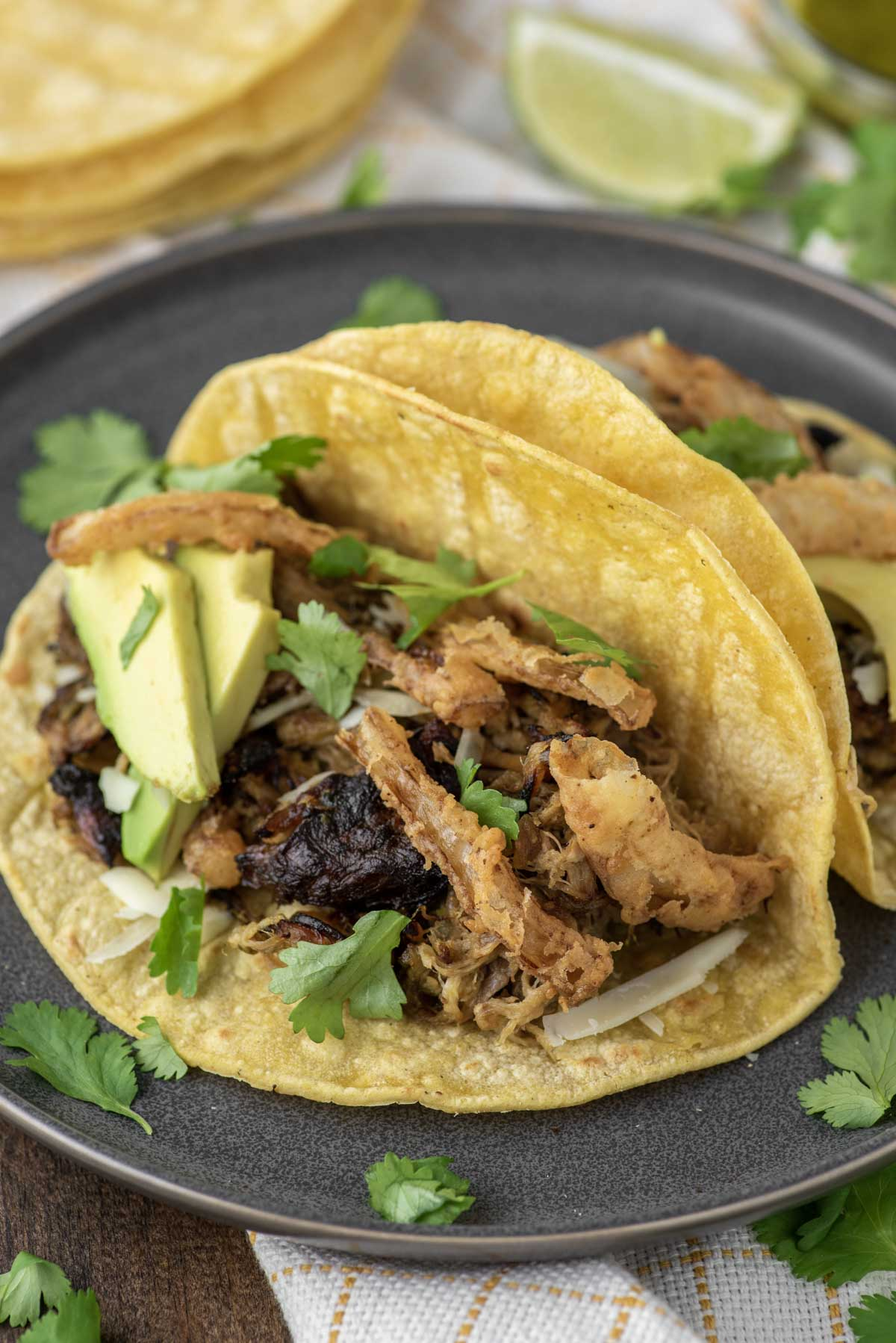 pork tacos with fried onions on slate grey plate