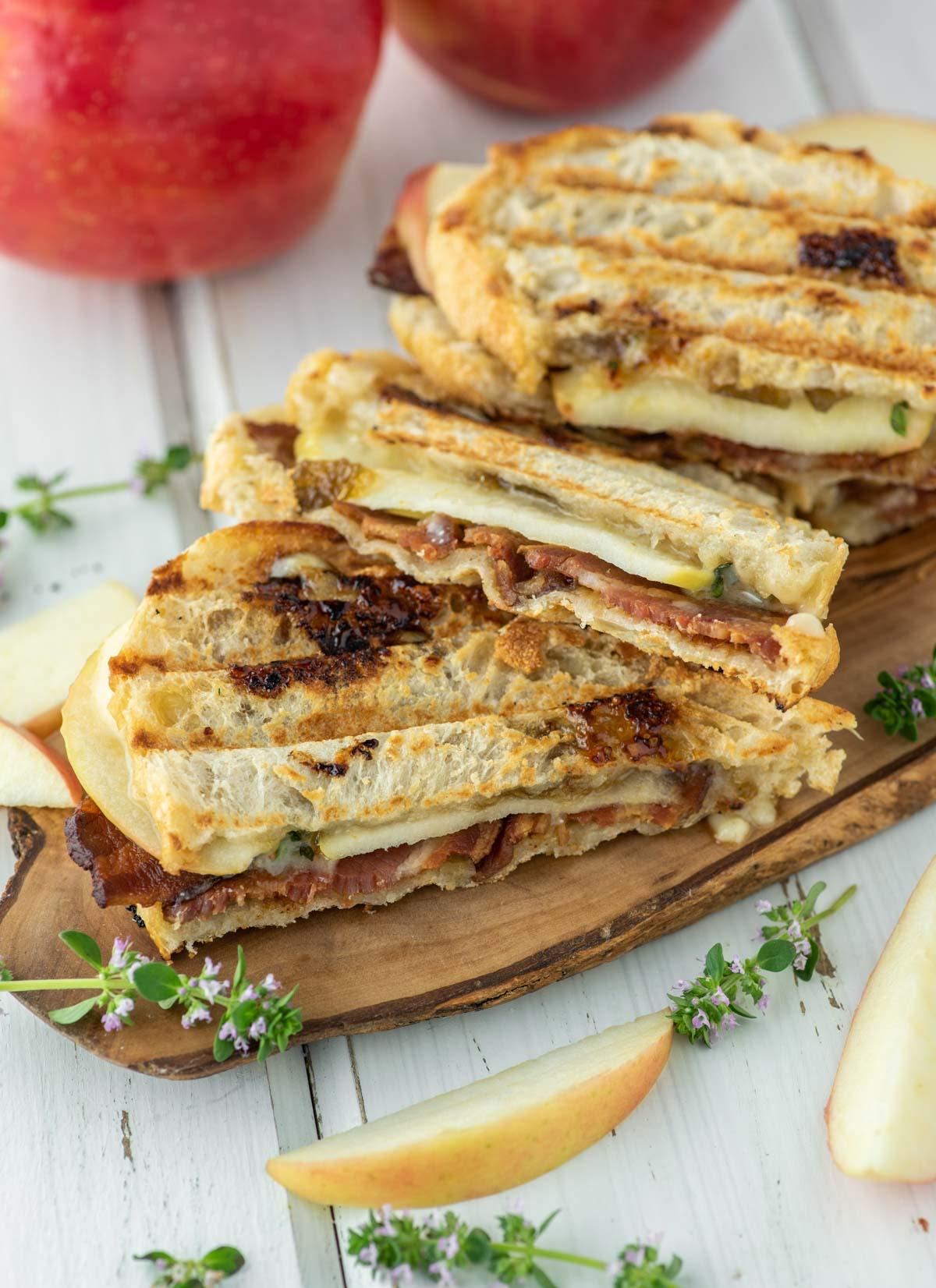 apple cheddar bacon paninis on wood board
