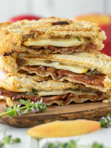 3 apple cheddar bacon paninis stacked on wood board