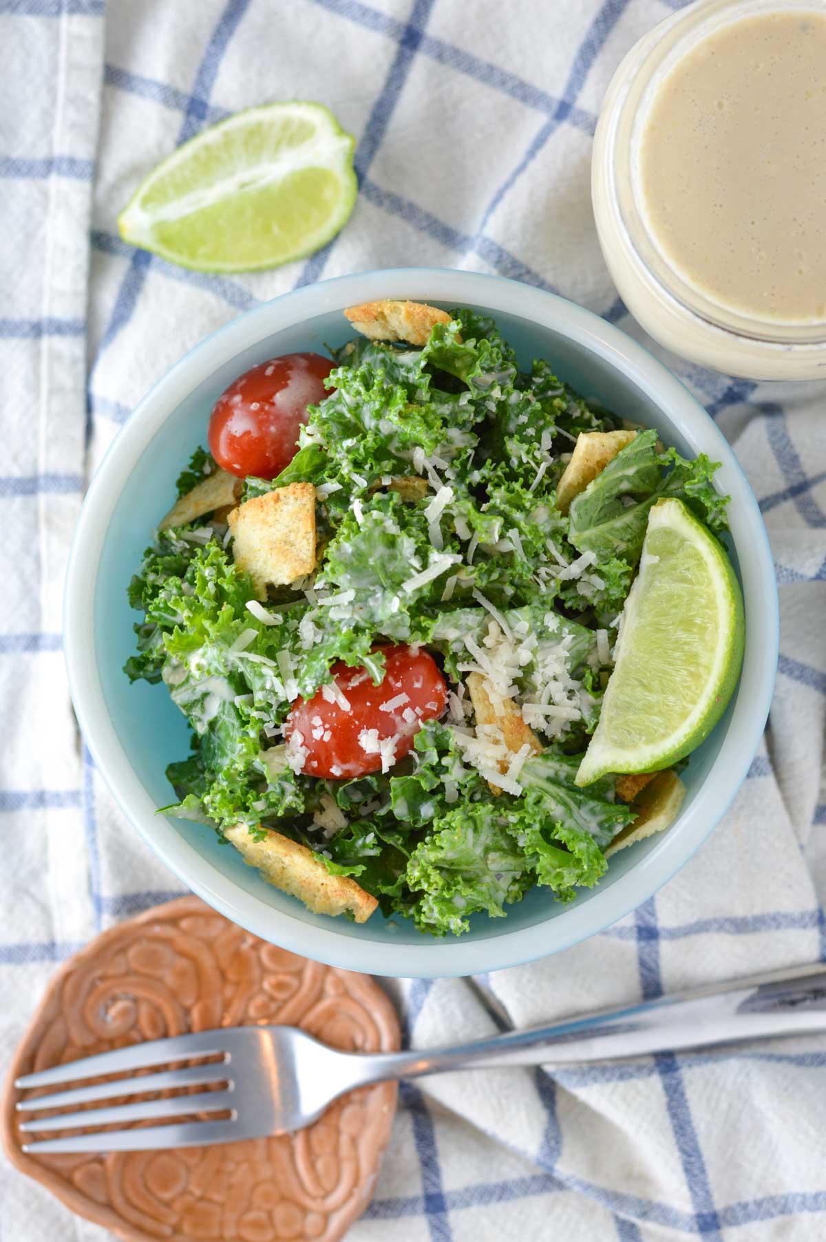 overhead shot of healthy kale caesar salad in blue bowl