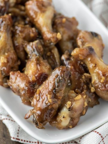 Vietnamese chicken wings on white plate with dish towel