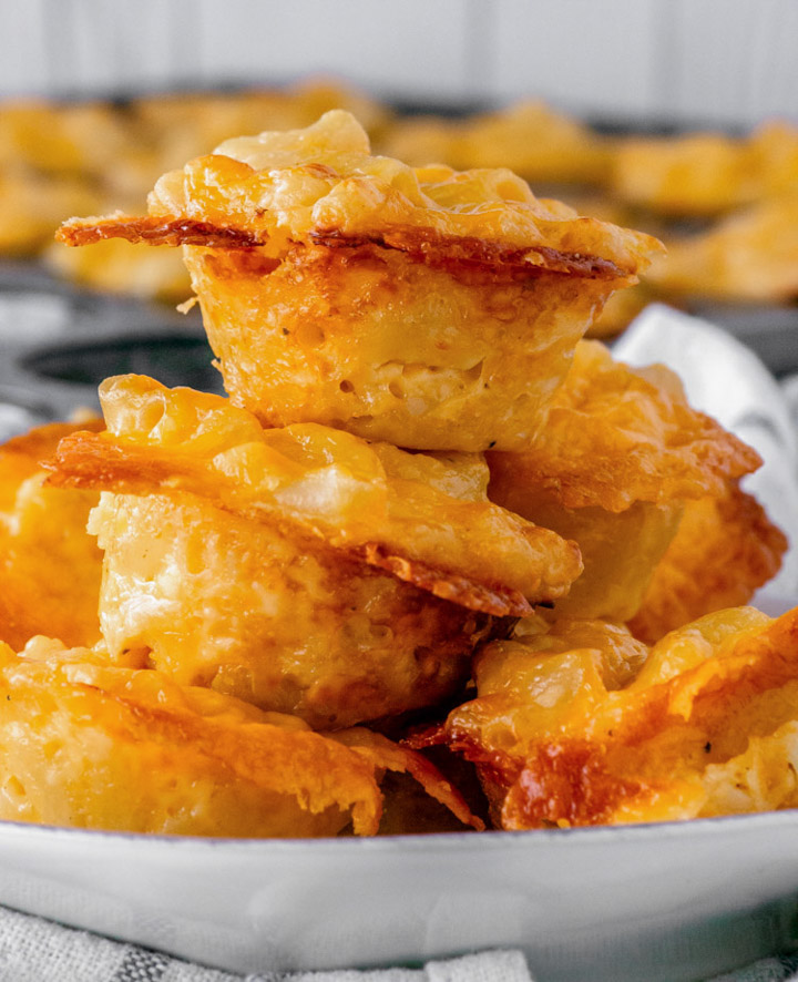 close-up of stacked baked mac and cheese bites on white plate