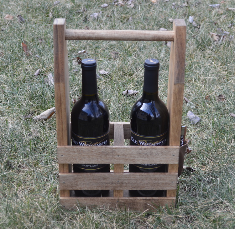 side view of wine caddy with 2 bottles of wine on grass