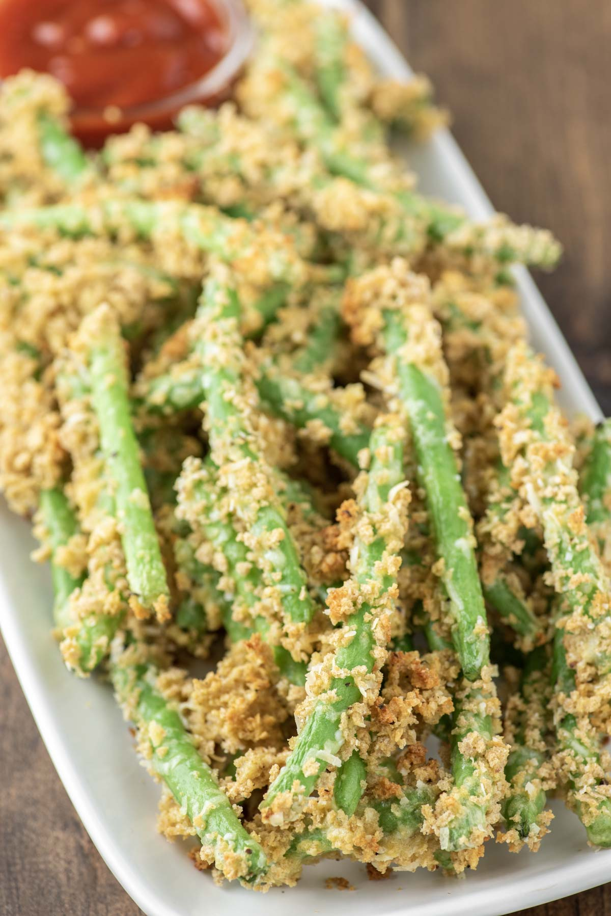parmesan green beans stacked on white plate