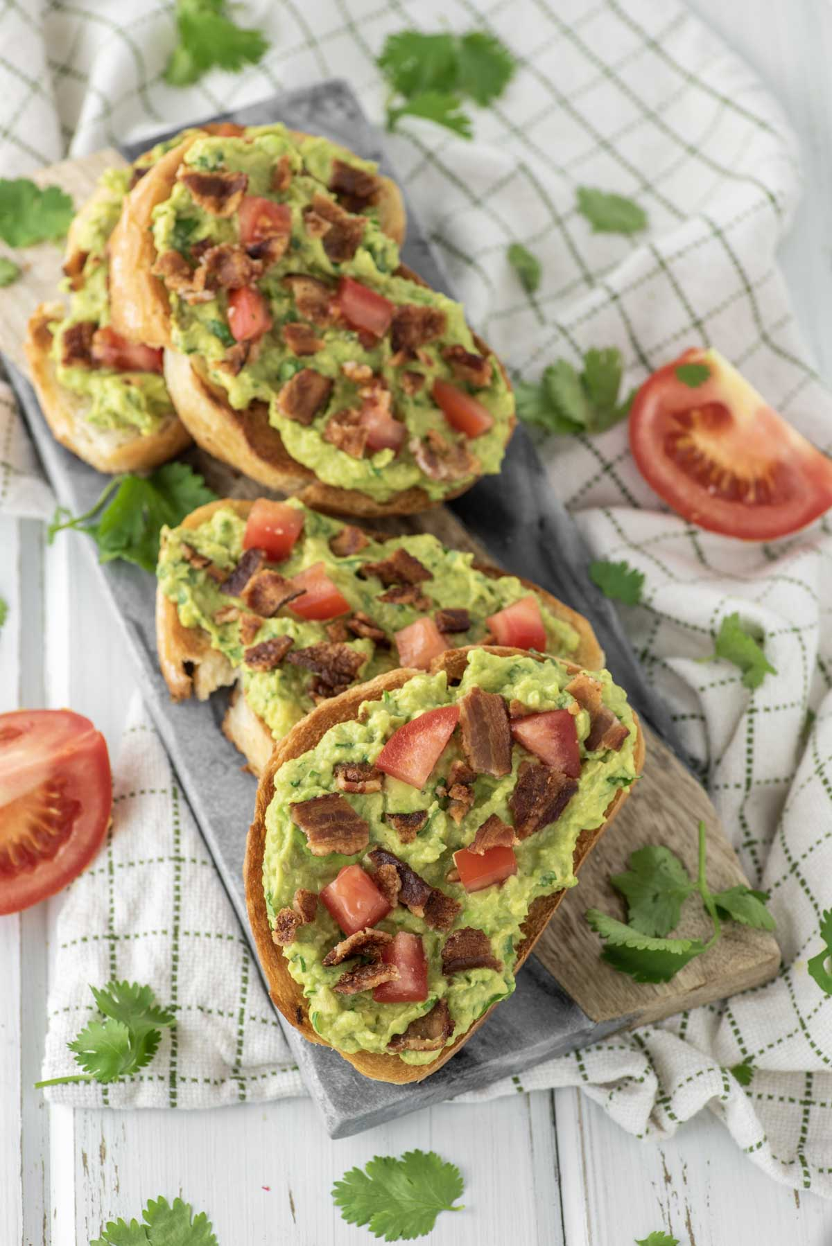 4 slices of bacon avocado toast on cutting board