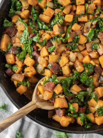 overhead shot of spoon dipped in chorizo sweet potato hash