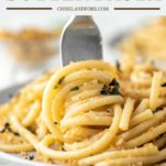 fork twirling garlic butter pasta on gray plate