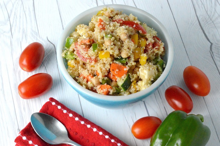 Summer quinoa salad in blue bowl with tomatoes and green pepper