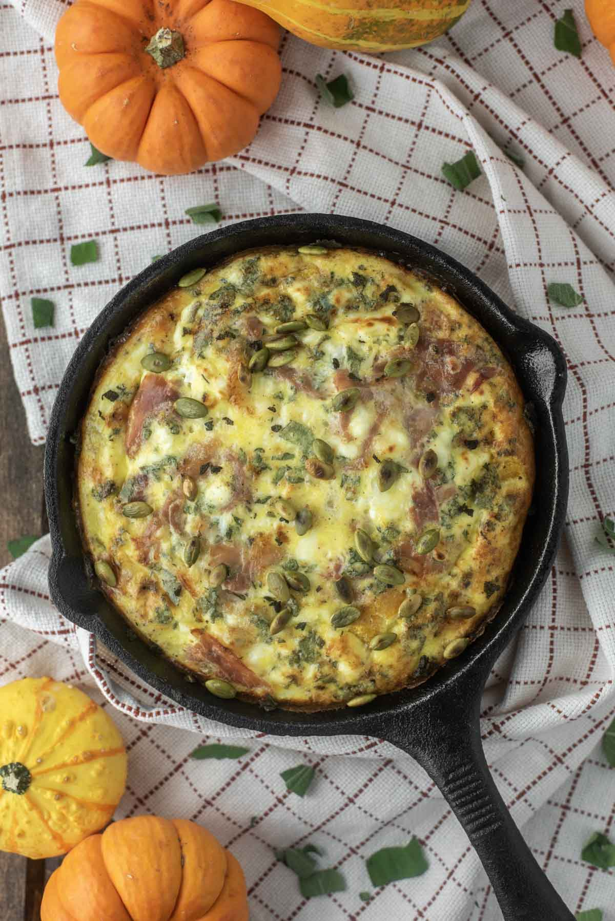 overhead shot of butternut squash frittata in cast iron skillet on dish towel