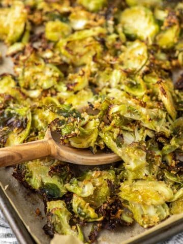 wooden spoon dipped in sheet pan of parmesan roasted Brussel sprouts