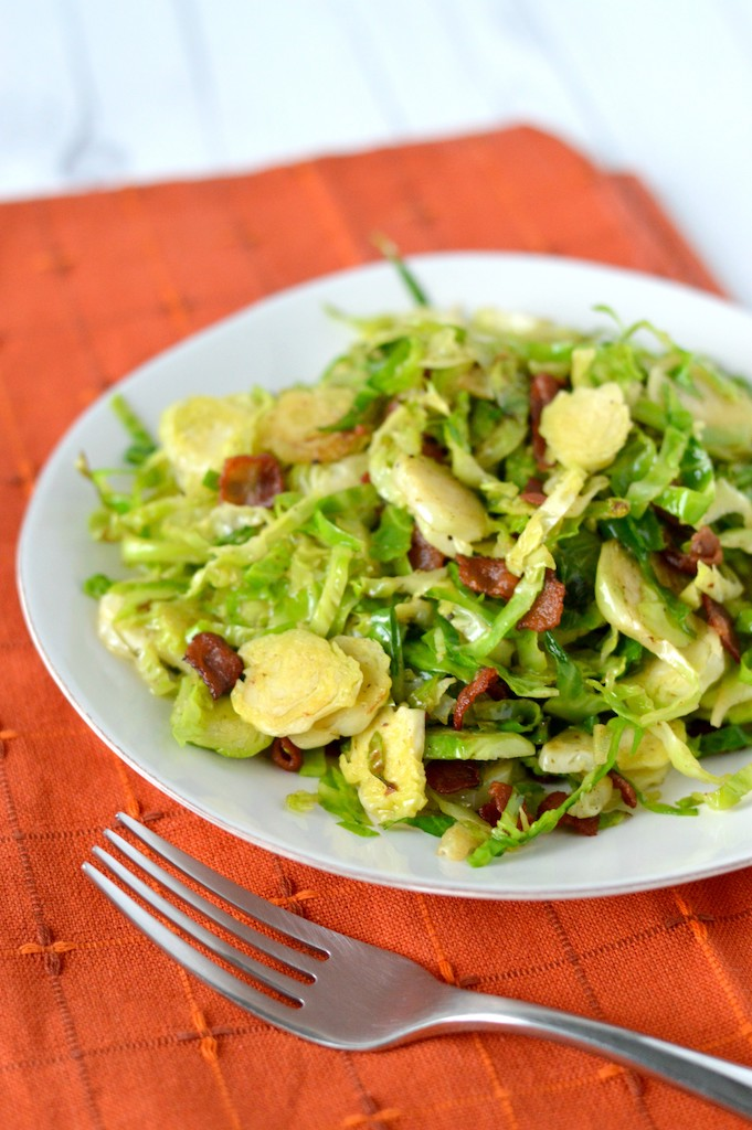 close-up of shaved brussels sprouts with bacon on white plate