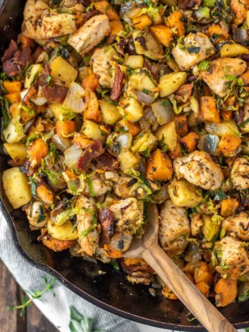 overhead shot of spoon dipped in sweet potato Brussels sprouts hash in skillet