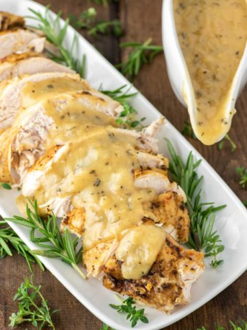 sliced instant pot turkey with gravy on white plate