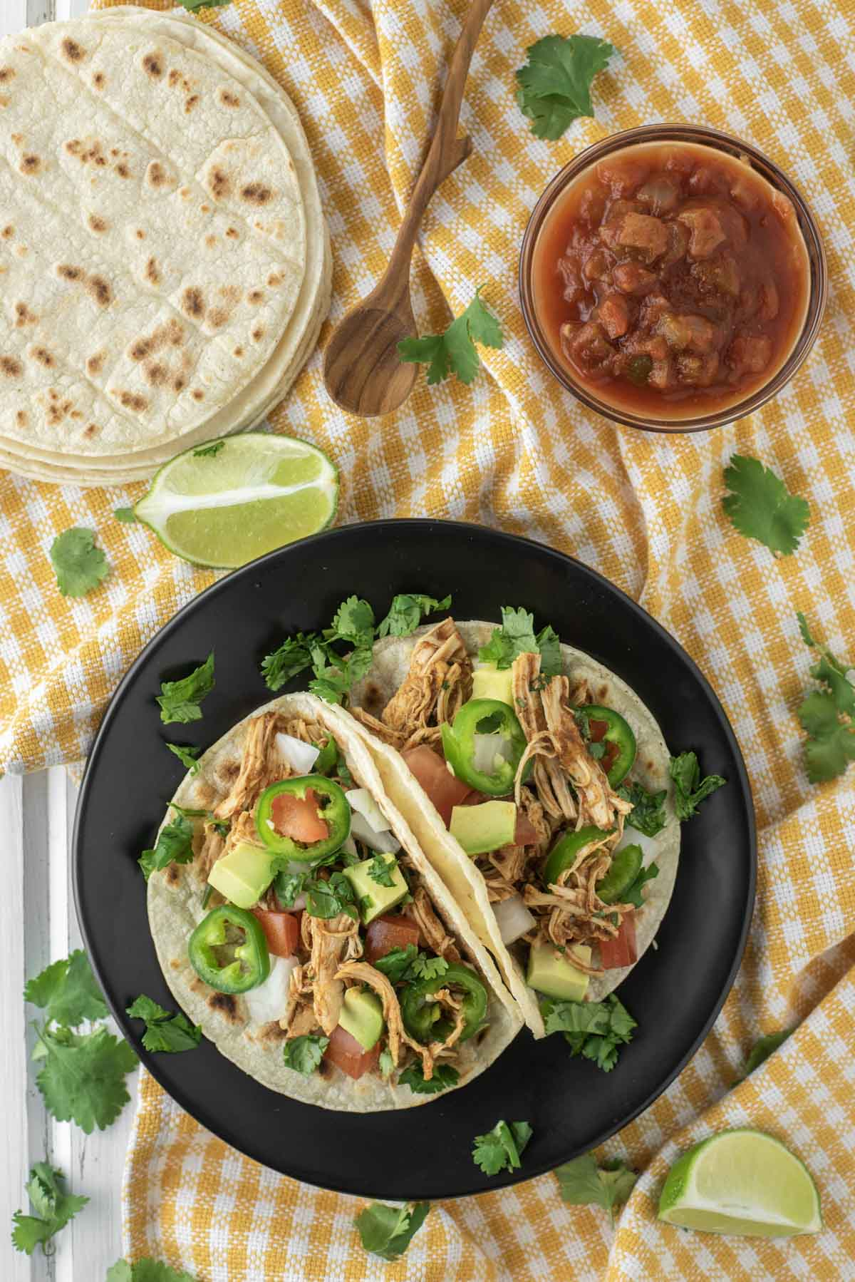 overhead shot of Instant Pot chicken tacos on black plate with salsa and extra tortillas