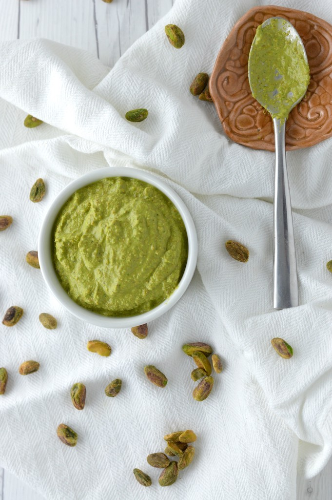 overhead shot of basil pistachio sauce in white ramekin