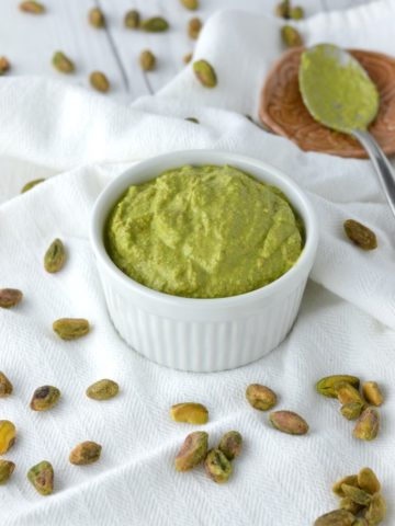 close-up of basil pistachio sauce in white ramekin