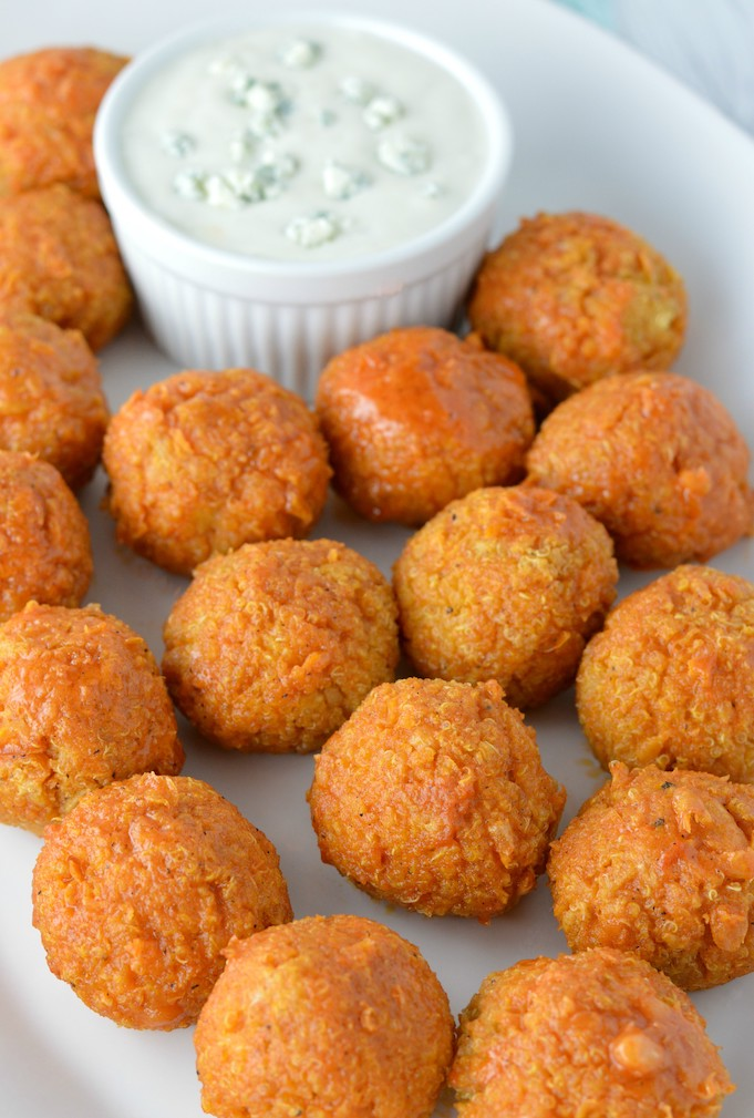 buffalo quinoa bites in white plate with blue cheese dressing in bowl