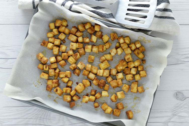 overlay of crispy baked tofu in baking sheet with spatula