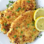 overhead shot of german chicken schnitzel on white plate