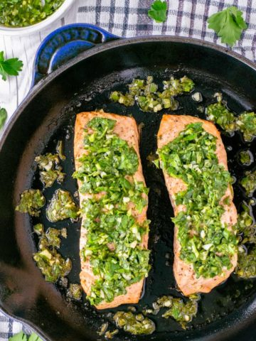 overhead of salmon with chimichurri in skillet
