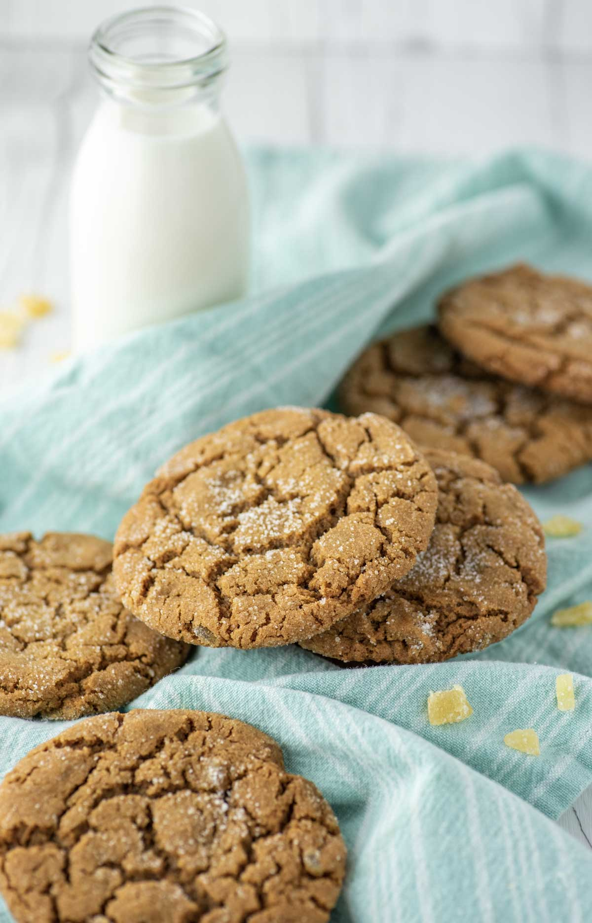 ginger cookies on teal dish towel with glass of milk