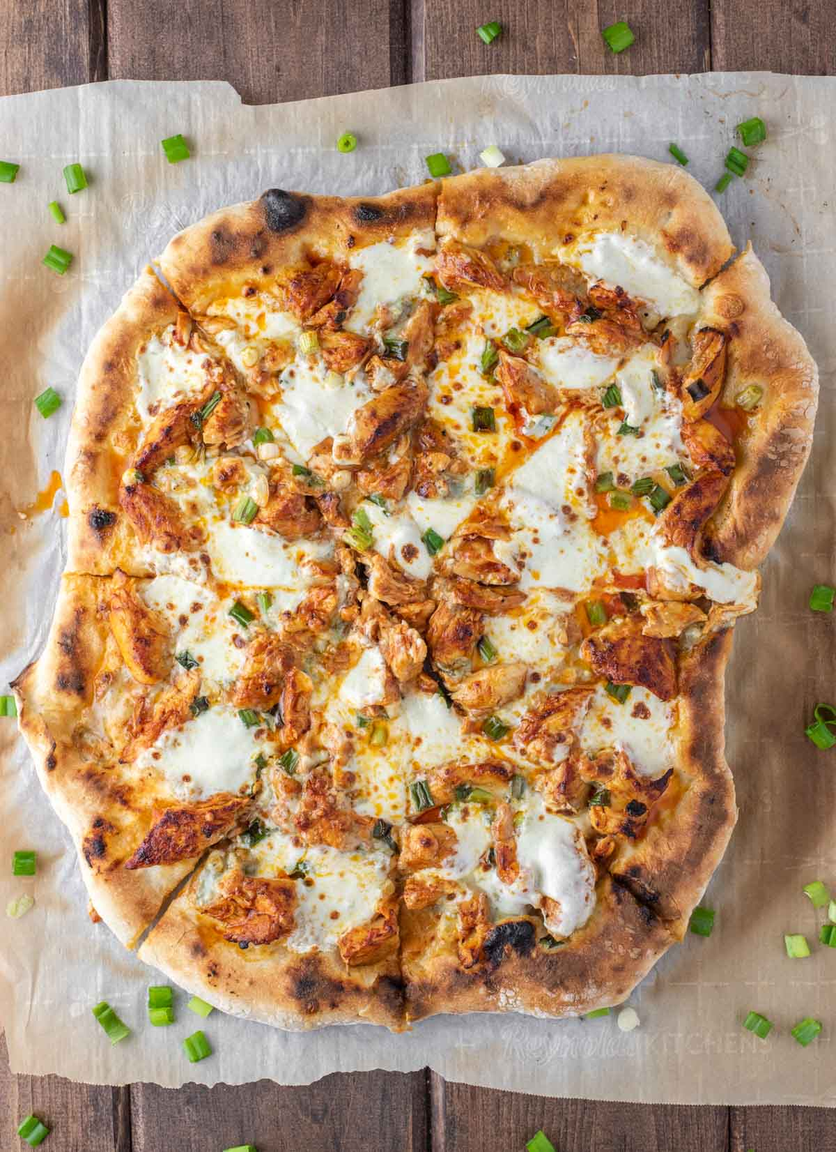 overhead shot of buffalo chicken pizza on parchment paper