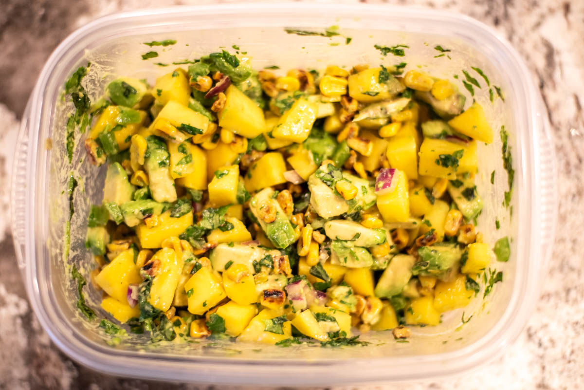 process shot of mixing corn mango salsa in bowl