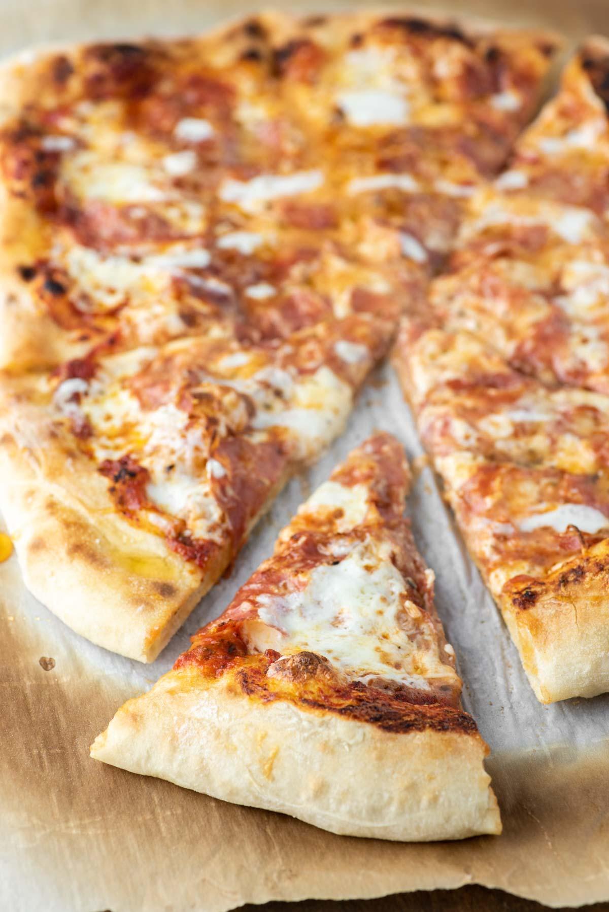 honey-drizzled salami pizza on parchment paper