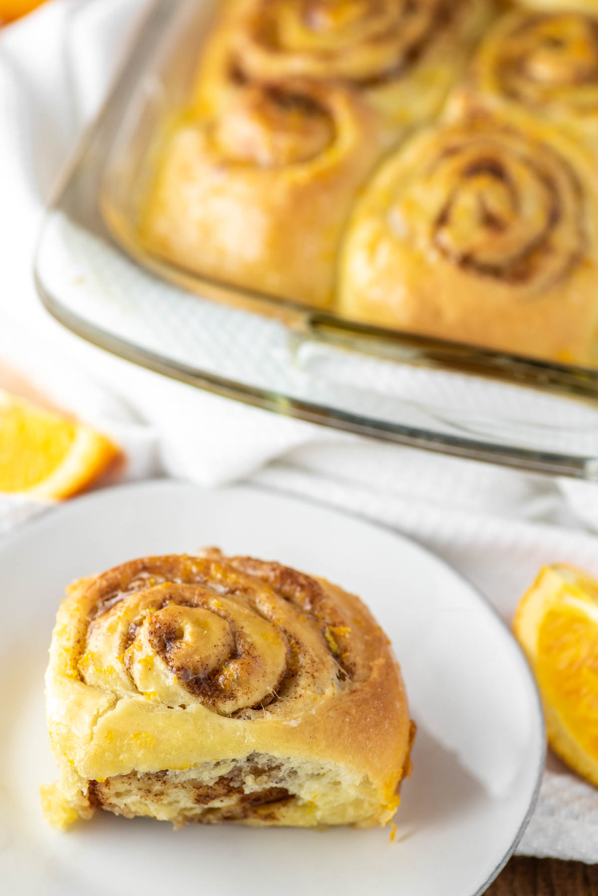 orange roll on white plate with rolls in baking dish in background