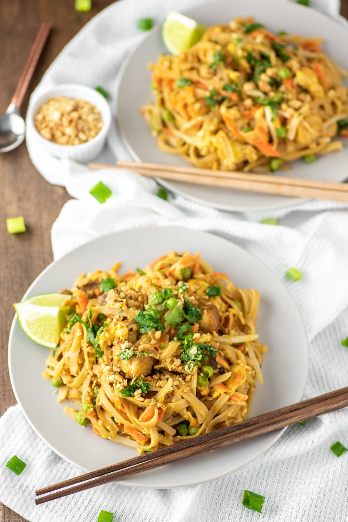 pad Thai on plate with another plate of pad Thai in background